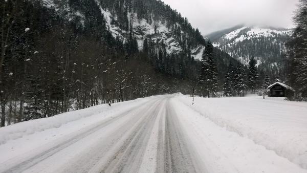 Schneebedeckte Straße im Ursrpungstal Richtung Bayrischzell